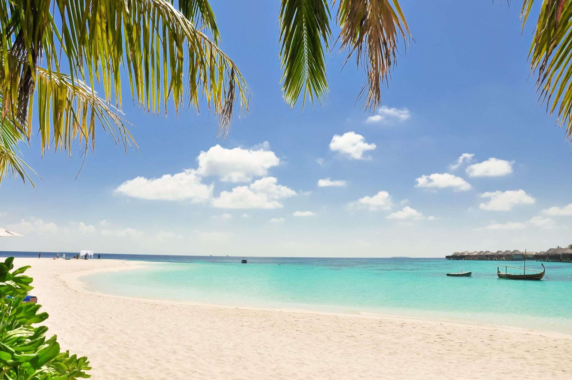 vacker kritvit sandstrand med klarblått vatten. På stranden finns det palmer.
